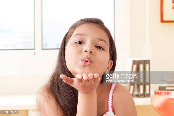 portrait of smiling girl blowing kisses - indian girl kissing stock photos and pictures
