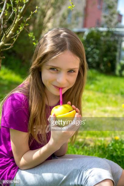 portrait of smiling girl drinking strawberry smoothie in garden - mädchen stock-fotos und bilder