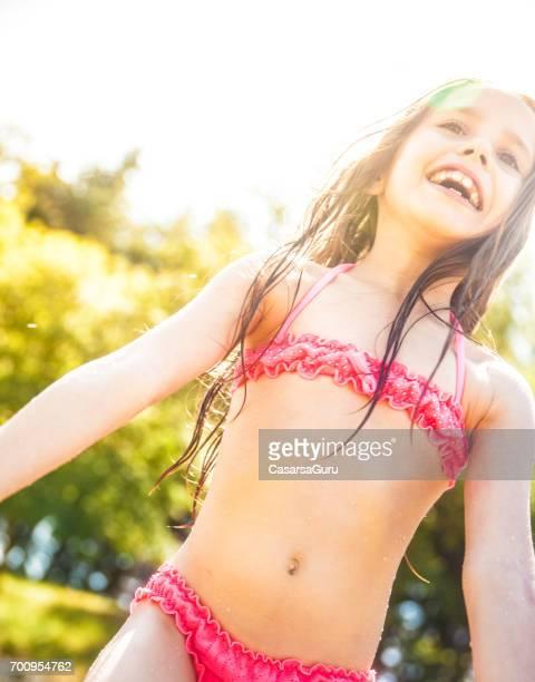 portrait of smiling girl enjoying her beach holiday - solo bambine femmine costume da bagno foto e immagini stock