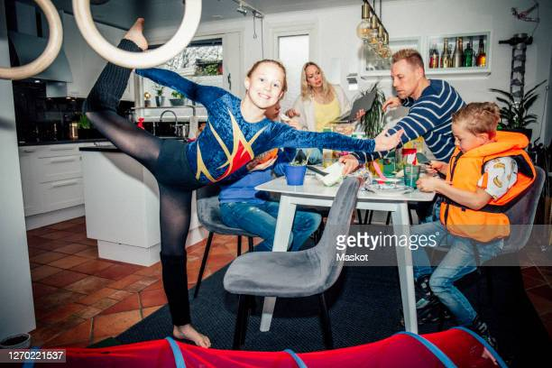 portrait of smiling girl exercising while family eating breakfast at table - gymnastics poses stock pictures, royalty-free photos & images