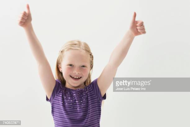 portrait of smiling girl gesturing thumbs up - human limb stock pictures, royalty-free photos & images