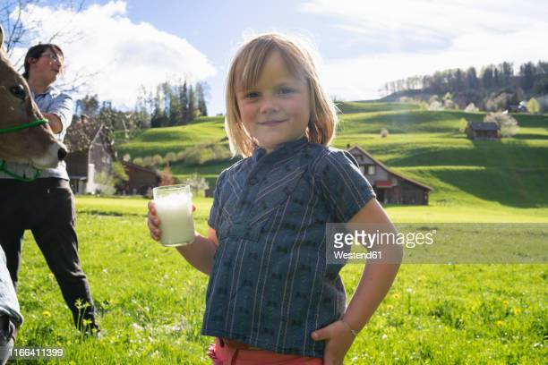 Portrait of smiling girl holding a glass of fresh milk on pasture