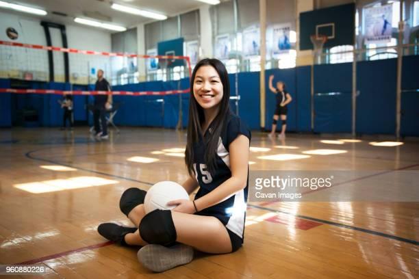 portrait of smiling girl holding ball and sitting on floor in volleyball court - caneleira roupa desportiva de proteção imagens e fotografias de stock