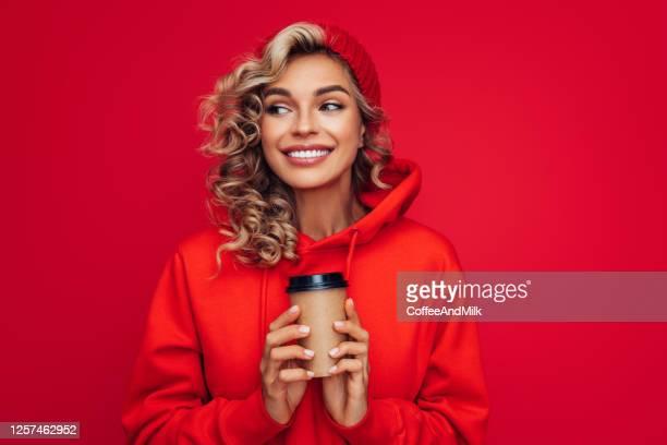 portret van glimlachend meisje dat wegwerpmok van koffie houdt - capuchon stockfoto's en -beelden