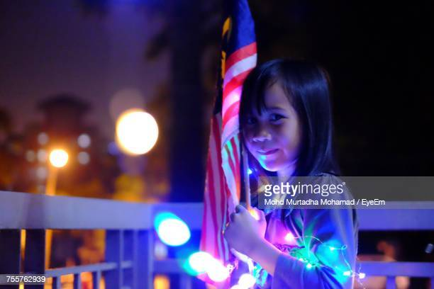 Portrait Of Smiling Girl Holding Flag At Night