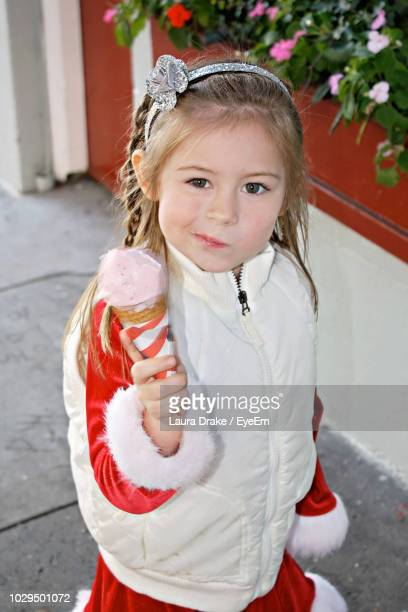 Portrait Of Smiling Girl Holding Ice Cream While Standing Outdoors