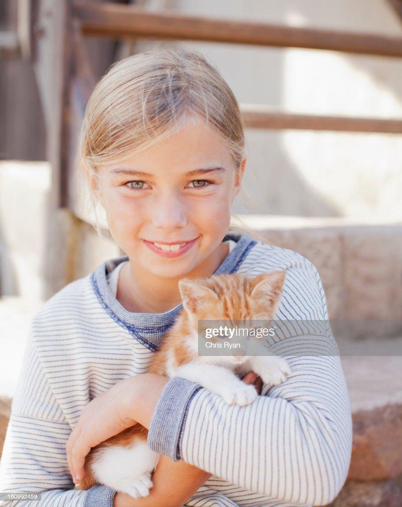 Portrait of smiling girl holding kitten : Stock Photo