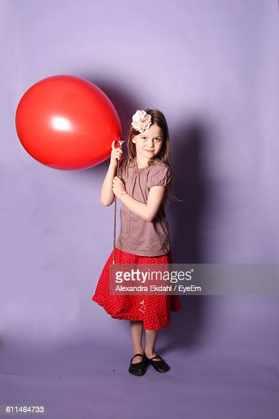 Portrait Of Smiling Girl Holding Red Balloon While Standing Against Purple Background