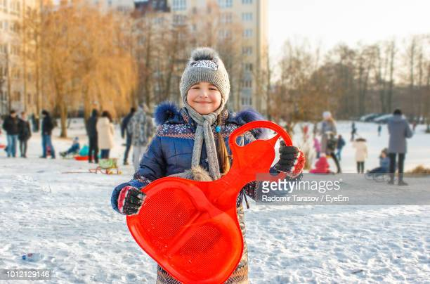 Portrait Of Smiling Girl Holding Sled On Snow Covered Field