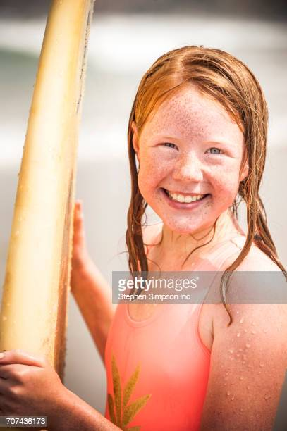 portrait of smiling girl holding surfboard - tween girls hot stock photos and pictures