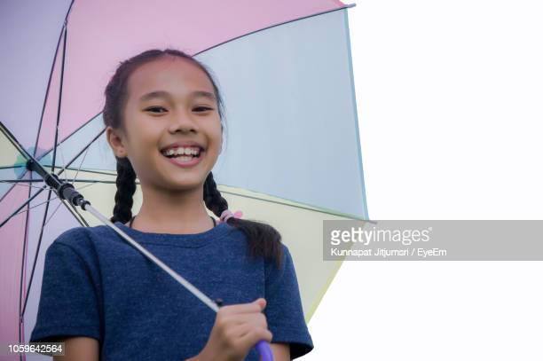 portrait of smiling girl holding umbrella - very young thai girls stock photos and pictures