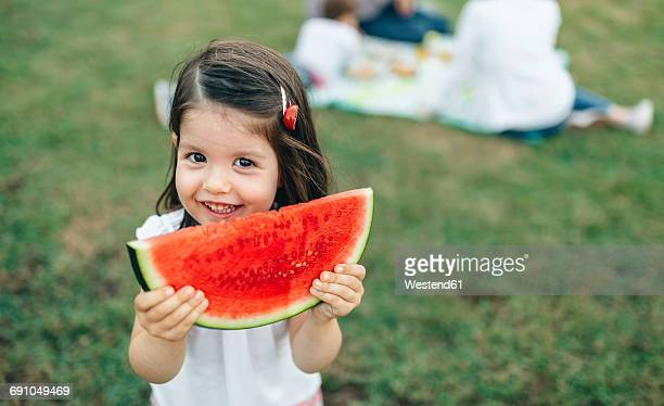 Portrait of smiling girl holding watermelon slice with her family in background