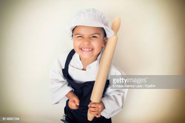 Portrait Of Smiling Girl In Chef Whites Holding Rolling Pin Against Wall