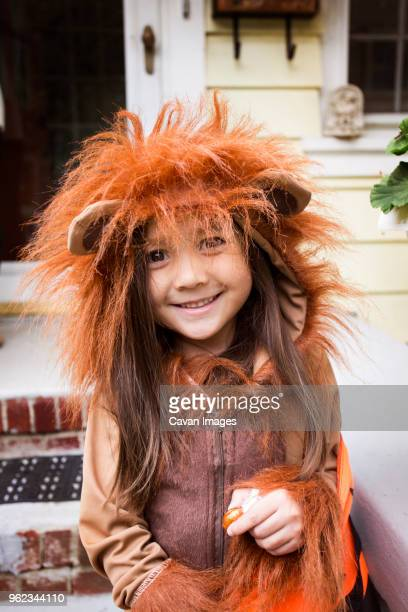 portrait of smiling girl in halloween costume standing against house - tradição - fotografias e filmes do acervo
