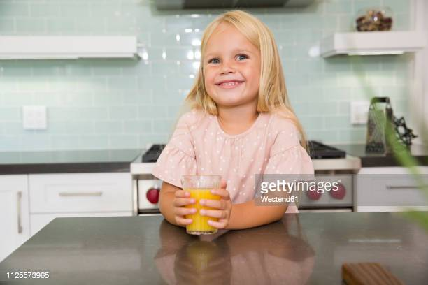 portrait of smiling girl in kitchen with glass of orange juice - blonde glasses stock-fotos und bilder