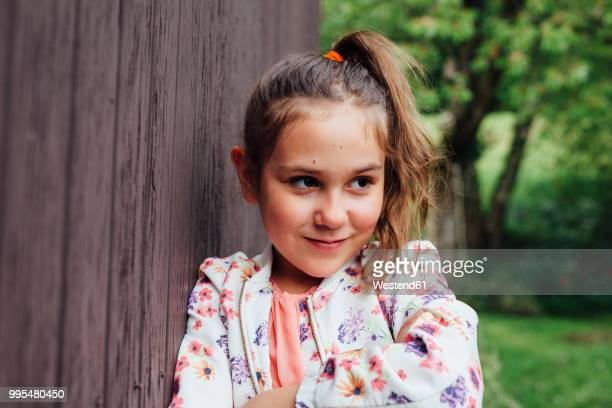 Portrait of smiling girl leaning against wooden wall