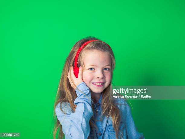 portrait of smiling girl listening music through headphones against green background - tête composition photos et images de collection