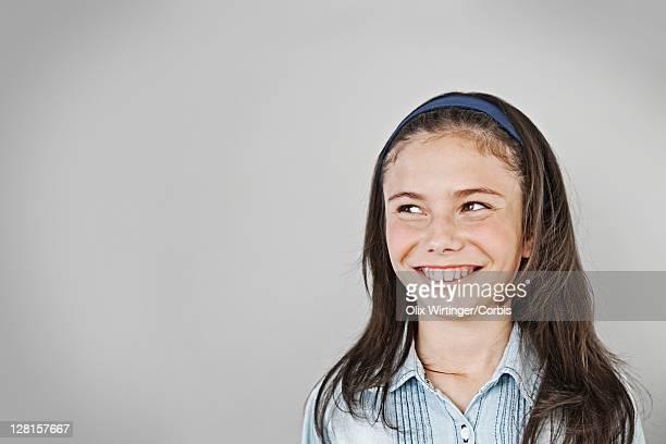 Portrait of smiling girl (10-12) looking away, studio shot