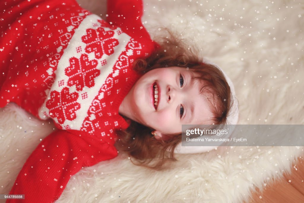 Portrait Of Smiling Girl Lying Down On Rug : Stock Photo