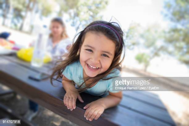 Portrait Of Smiling Girl Lying Down On Table