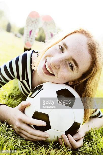 Portrait of smiling girl lying on a meadow with head on soccer ball