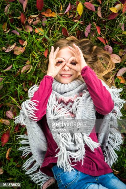 Portrait of smiling girl lying on autumnal meadow looking through her fingers formed like spectacles