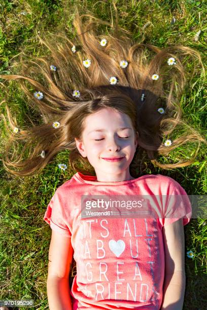 Portrait of smiling girl lying on grass in spring with daisies on hair