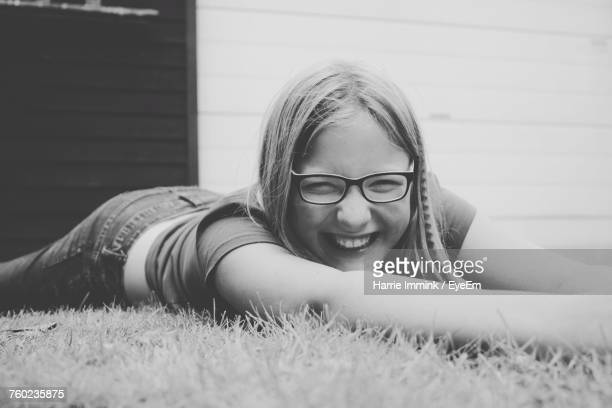 portrait of smiling girl lying on grass - lying on front stock pictures, royalty-free photos & images