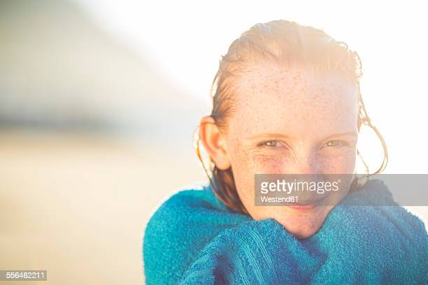 Portrait of smiling girl on the beach wrapped in a beach towel