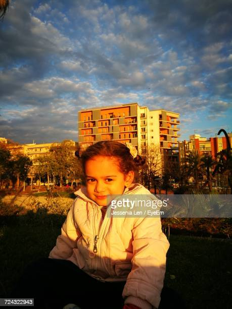 portrait of smiling girl sitting at lawn against buildings in city - jessenia stock pictures, royalty-free photos & images