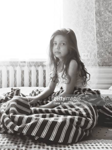 portrait of smiling girl sitting on bed at home - elena knouzi stock pictures, royalty-free photos & images