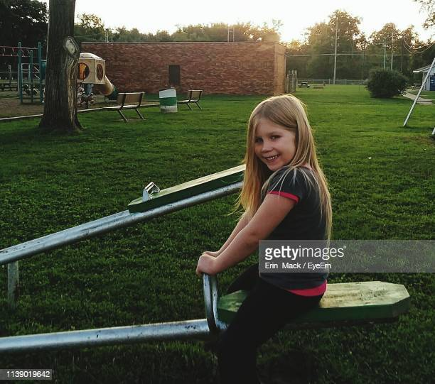 portrait of smiling girl sitting on seesaw in park - mack stock pictures, royalty-free photos & images