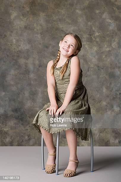 Portrait of smiling girl (8-9) sitting on stool