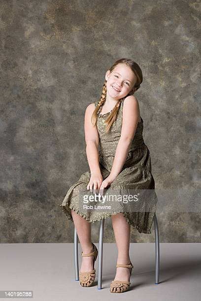 Portrait of smiling girl (8-9) sitting on stool, studio shot