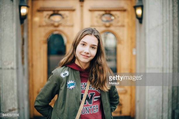 portrait of smiling girl standing against building - bambine femmine foto e immagini stock