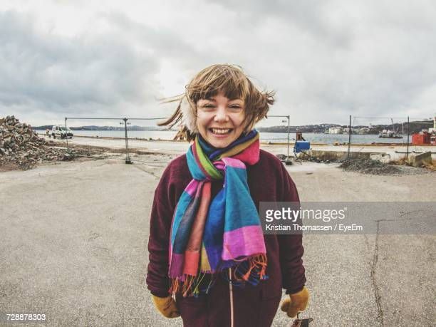 Portrait Of Smiling Girl Standing Against Cloudy Sky