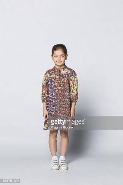 Portrait of smiling girl standing against white background