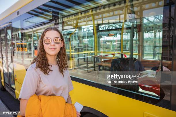 portrait of smiling girl standing by bus - val thoermer stock-fotos und bilder