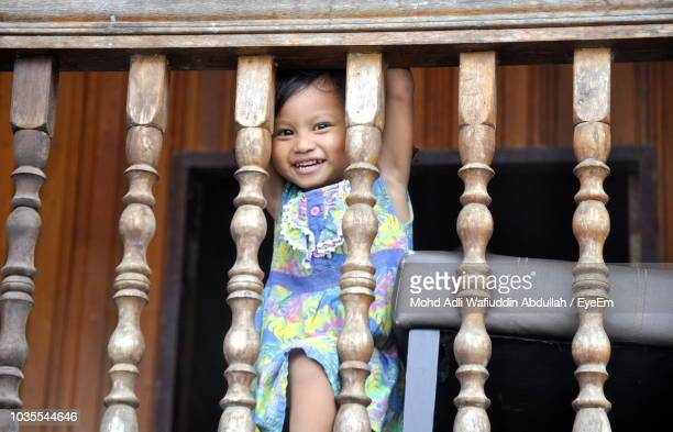 Portrait Of Smiling Girl Standing By Railing