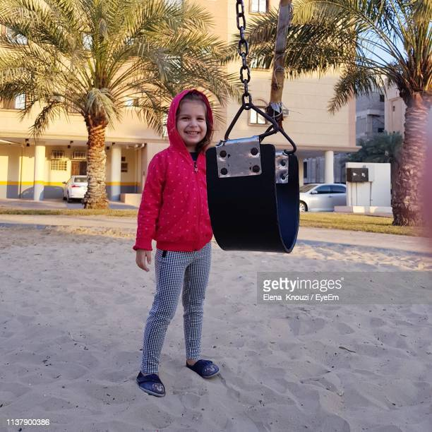 portrait of smiling girl standing by swing on sand - elena knouzi stock pictures, royalty-free photos & images