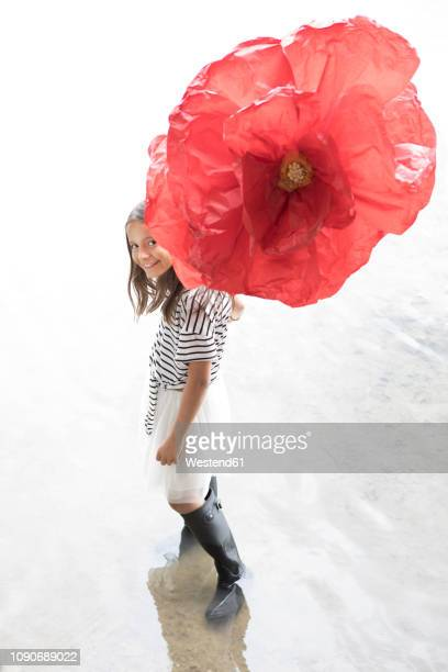 Portrait of smiling girl standing in a lake with oversized red artificial flower