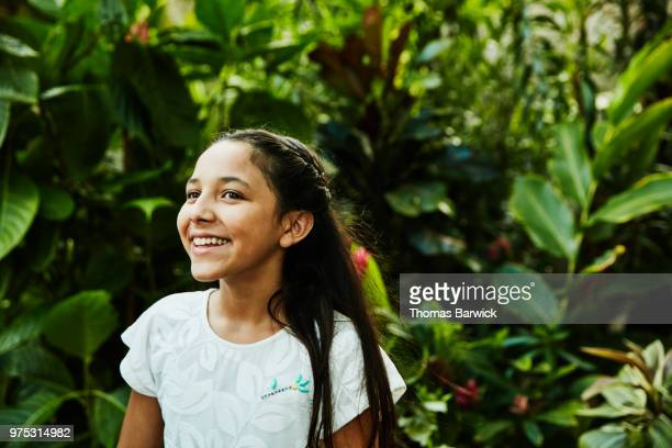 Portrait of smiling girl standing in backyard garden
