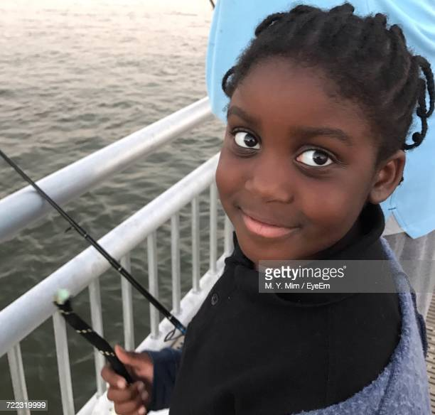 Portrait Of Smiling Girl Standing In Boat Over Sea