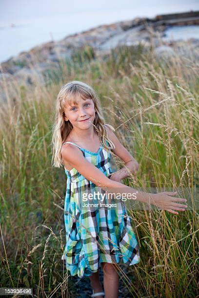 Portrait of smiling girl standing in tall grass
