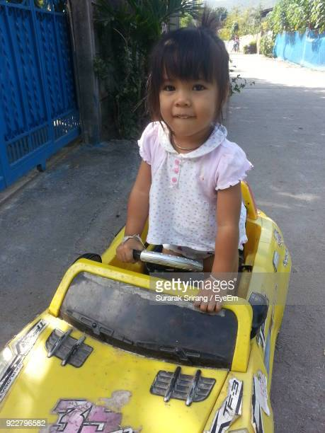 Portrait Of Smiling Girl Standing In Toy Car On Road