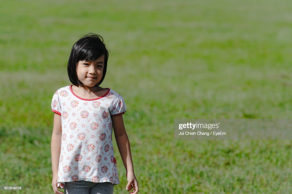 Portrait Of Smiling Girl Standing On Field : Stock Photo