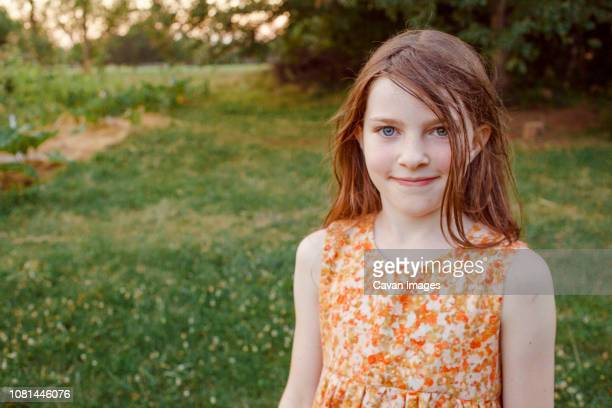 Portrait of smiling girl standing on grassy field at farm