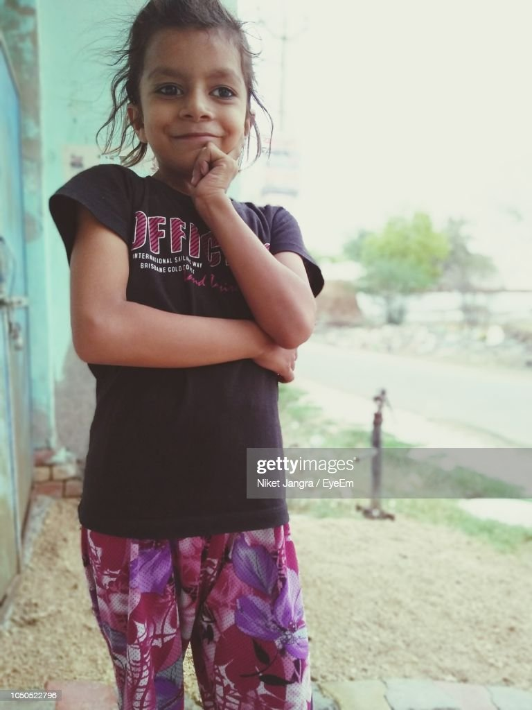 Portrait Of Smiling Girl Standing Outdoors Stock Photo