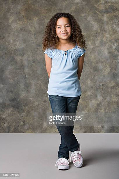 Portrait of smiling girl (8-9) standing, studio shot