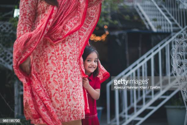 Portrait Of Smiling Girl Standing With Mother Against Steps
